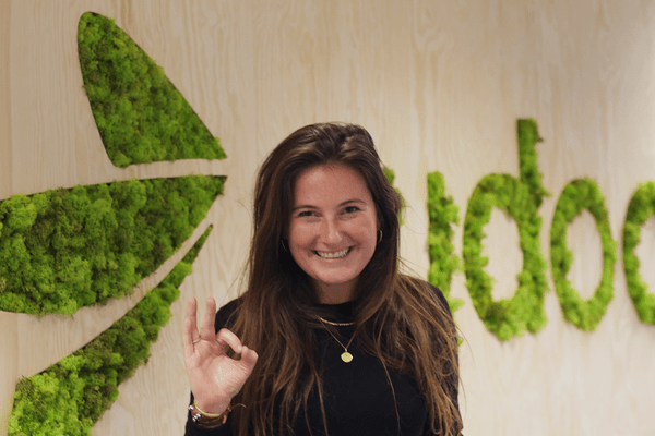An happy Rydooer smiling in front of the Rydoo logo made with grass